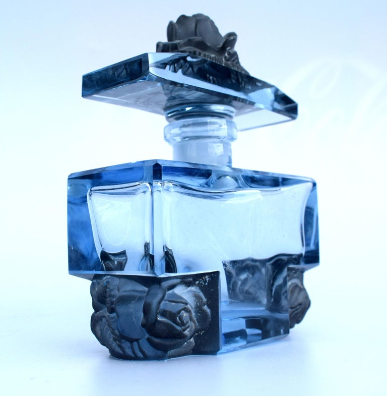 A truly beautiful blue glass 1930s ladies perfume bottle decorated with moulded floral brackets as floral friezes in which also serve as feet the recessed box shape. Most likely this piece is made by the Czech glass maker Josef Hofmann, very