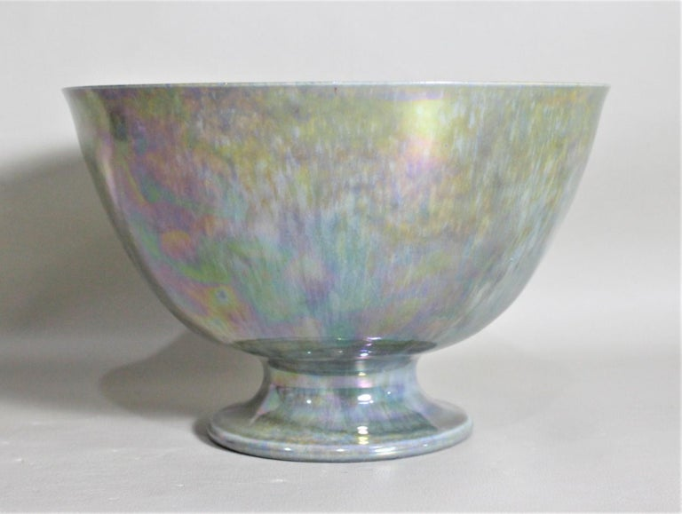 This vibrant blue iridescent bowl was made by the Ruskin Pottery factory of England in circa 1935 in the period Art Deco style. The bowl has a light blue glaze with strong iridescence both on the inside and outside of this pedestal bowl. The bowl is