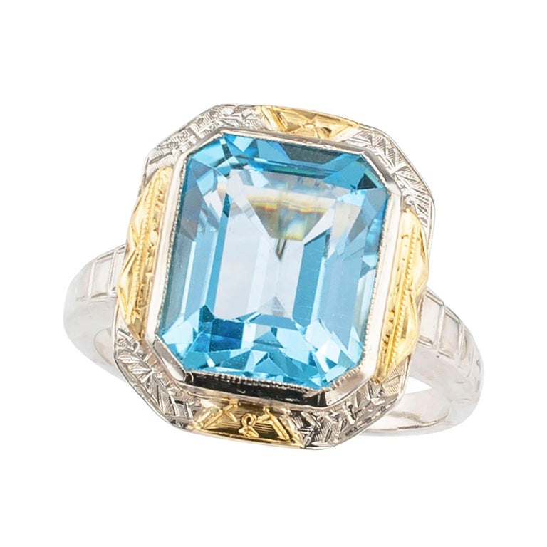 """Art Deco blue topaz and two-tone gold ring circa 1930.  DETAILS: GEMSTONE: one emerald-cut blue topaz.  METAL: white and yellow 14-karat gold.  RING SIZE: approximately 5 ¾, can be resized.  MEASUREMENTS: approximately 9/16"""" (14 mm) wide across the"""