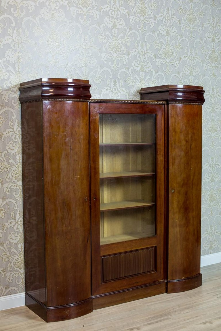 We present you this three-door piece of furniture. The central section is lower, glazed on the three quarters of its height. The corner segments with full doors with semi-circular fronts. The top of this bookcase is finished with a molding with