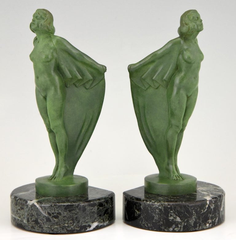 Art Deco bookends nude with cape by Max Le Verrier. The sculptures are executed in Art metal and have a lovely green patina. They are mounted on green marble circular bases. France 1930. 