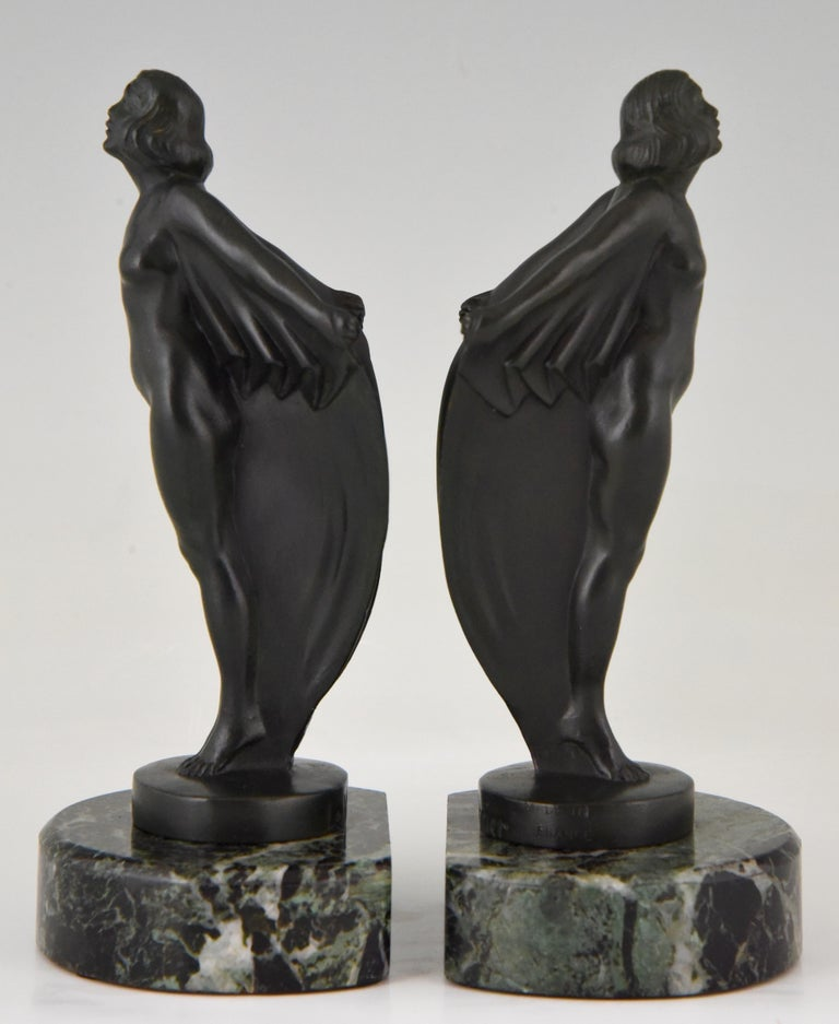 A lovely pair of Art Deco standing nudes with drape by the famous French sculptor Mar Le Verrier. The women are cast in Art metal and have a dark green patina. They are mounted on a green marble base, France, 1930.