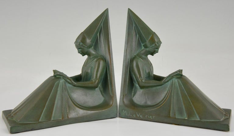 """A pair of Art Deco bookends modelled as seated medieval ladies reading a book. The stylish sculptures have a lovely green patina and are signed by the famous sculptor Max Le Verrier, France, circa 1930. """"Art Deco sculpture"""" by Victor Arwas,"""