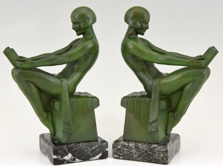 A pair of Art Deco bookends with reading nudes by Max Le Verrier, France 1930. The Art metal sculptures have a lovely green patina and are mounted on Portor marble bases.   Literature: