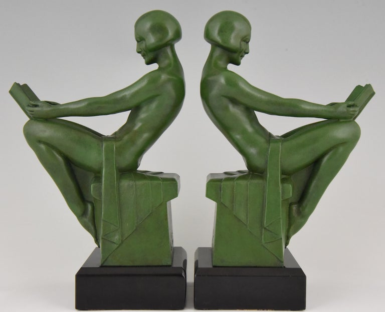Stylish pair of Art Deco bookends with reading nudes. Signed by the famous French artist Max Le Verrier. Patinated green Art metal on Belgian Black marble base, circa 1930.