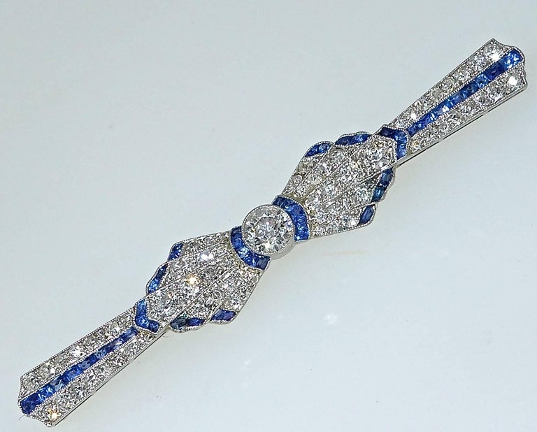 Platinum (with a gold pin stem), this brooch has fine diamonds and fancy cut fine blue sapphires.  The pin is 2.50 inches long and centers a .50 ct old cut diamond.  The 45 French cut fine natural sapphires are a bright blue and weigh approximately