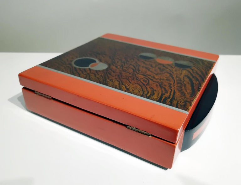 Decorative wood box with a hinged lid. The top is decorated in a typical distinctive geometric Art Deco style, having a brown, black and orange finish.  Can be used as a jewelry or trinkets box on the desk or dressing table.