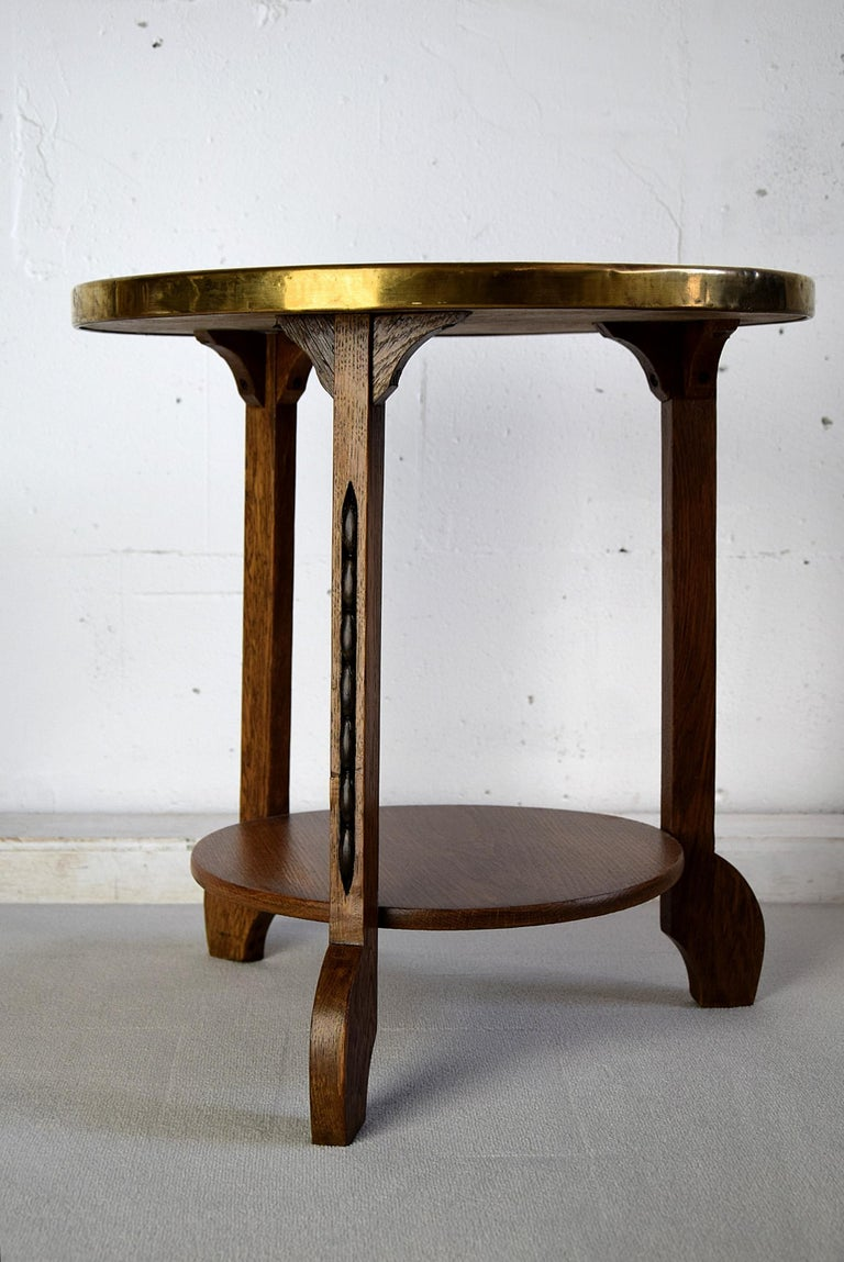 Rare 1920s Art Deco brass and oak side table with decorated brass top. This piece was produced in the Netherlands circa 1920. The table top was made in Persia and brought to the Netherlands by traders. Than the top was used by Artigiani who turned