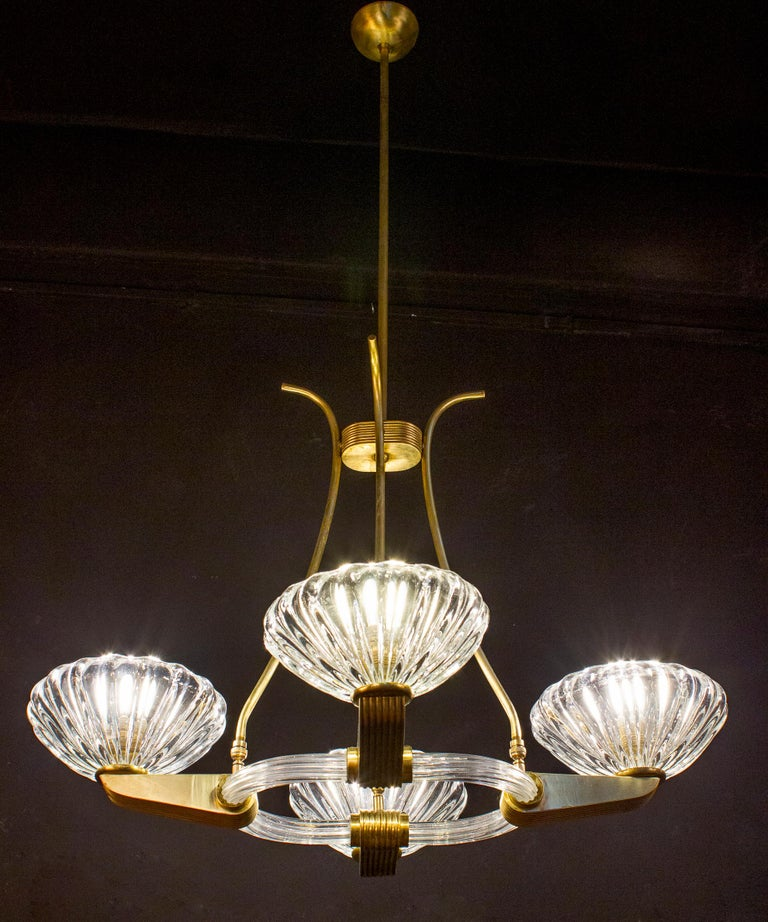 Elegant four-shade Murano glass chandelier with elegant shaped brass mount, by Ercole Barovier. Excellent vintage condition. Four E 27 light bulbs compatible with US standards. The height of the brass rod can be shortened.
