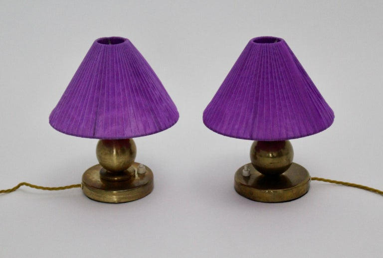 This presented pair of brass Art Deco vintage table or bedside lamps shows a brass base and a renewed lilac organza fabric lamp shade. The brass bases are in very good vintage condition with signs of age and use and feature a great brass patina.