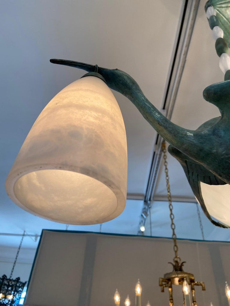 Art Deco style bird chandelier, cranes cast in bronze, made with custom alabaster lantern style shades on rods.