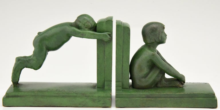"""Sit and push"" Art Deco bronze bookends boy and girl satyr.
