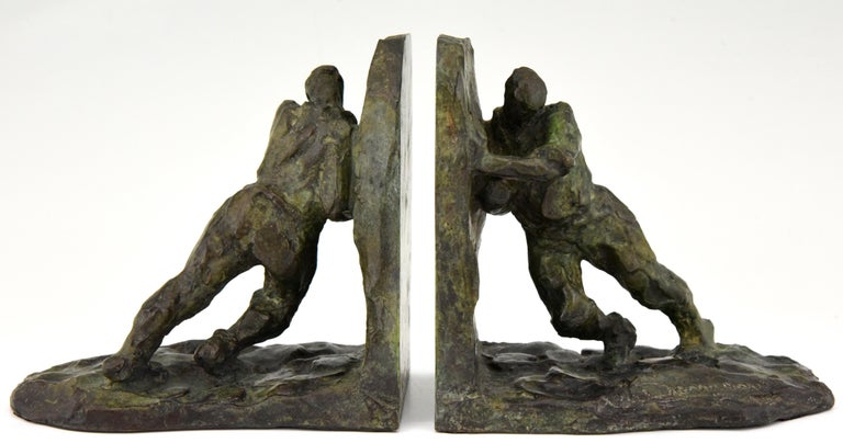 Art Deco bronze bookends picturing two men pushing, France, 1925.  Signed by the well known sculptor Victor Demanet. The artist was born in 1895 and worked in Belgium and France.  The bronzes have a lovely green patina with lighter shades.