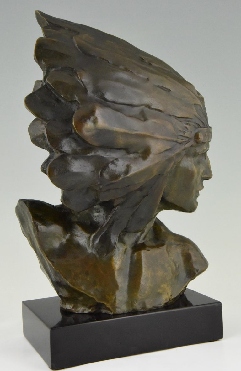 Stunning Art Deco bronze bust of an Indien with headdress. Signed by the French artist L. Sosson. The sculpture has a lovely green patina and stands on a Belgian Black marble base. Ca 1930.   Literature: