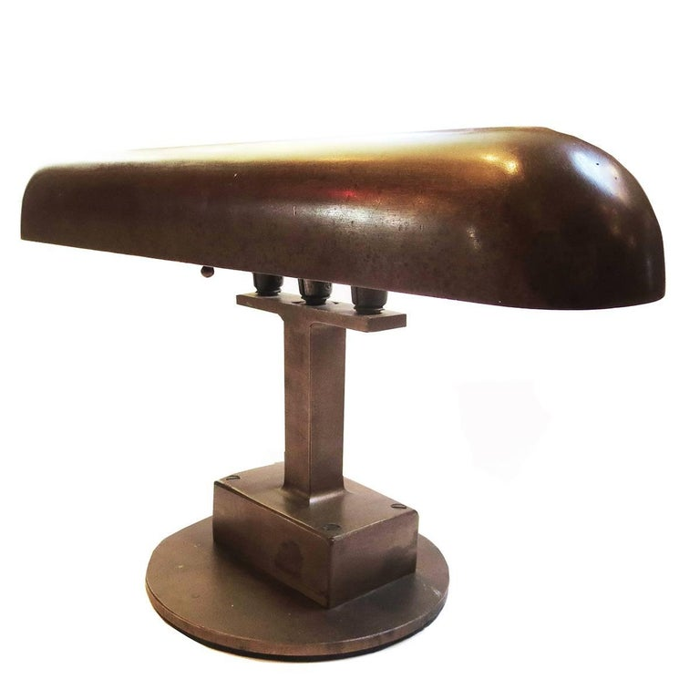 "This wonderful lamp is a fantastic example of ""machine age"" design.It is extremely well built, and heavy and solid. Although the designer is not known, it appears to be American in origin. The cast bronze shade houses two standard bulbs, an"