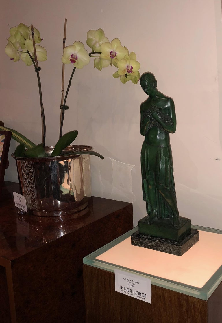 Classic 1920s Art Deco bronze statue of young female holding bouquet of flowers in draped skirt. Belgian artist Antoine Vriens (1902-1987) known for female statues but also famous for medallions. This is an extremely rare piece of which only 6