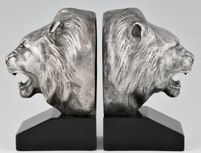 """A beautiful pair of Art Deco bronze lion bookends by the French sculptor Georges Raoul Garreau, ca. 1930. The lions are executed in bronze with a silver patina and are mounted on fine Belgian black marble bases  Literature: """"Dictionnaire illustré"""
