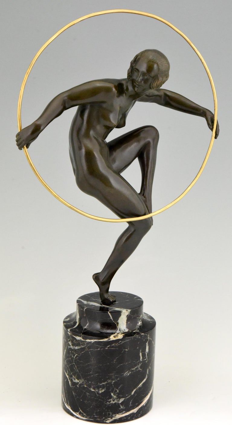 Girl with hoop. Nude dancing on one leg holding a hoop. Artist/ Maker: Marcel André Bouraine, 1886-1948.  Signature/ Marks: A. Bouraine. Style: Art Deco. Date: circa 1930. Material:  Patinated bronze on a marble base.  Origin: