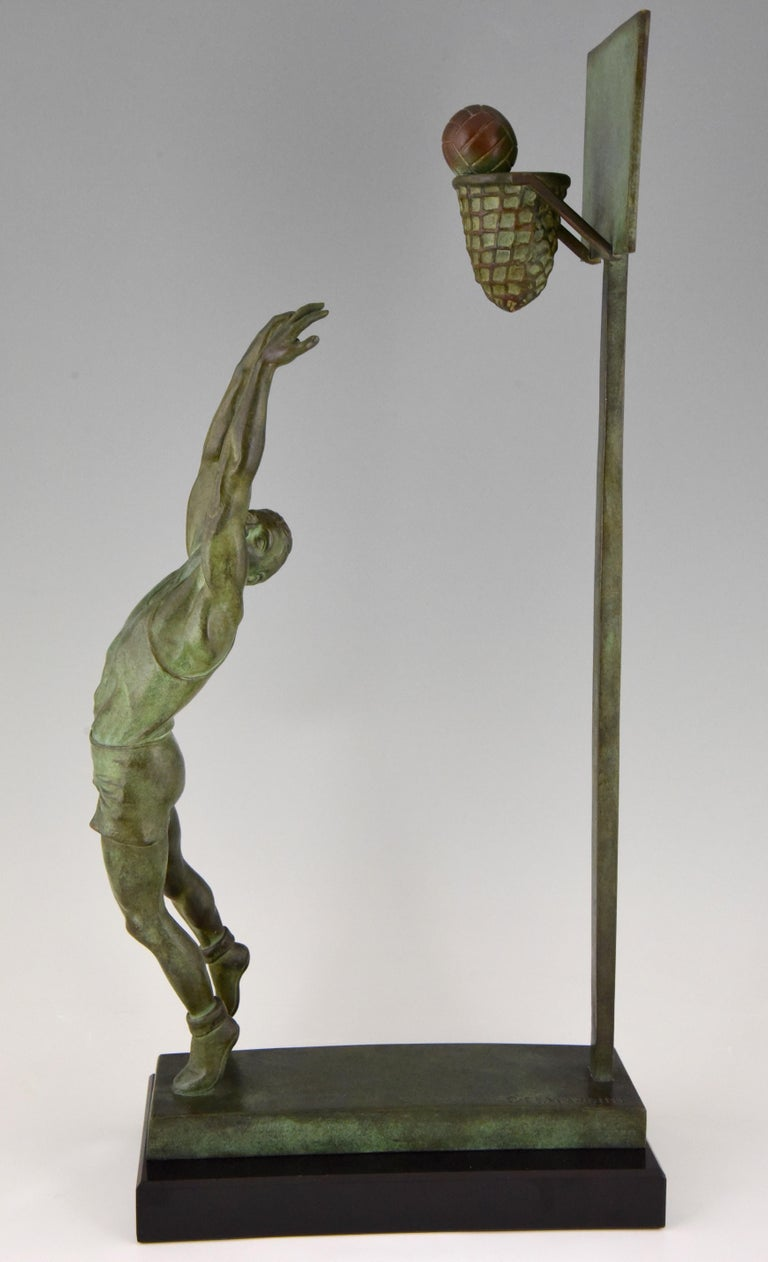 Hard to find Art Deco bronze sculpture of a basketball player doing a reverse dunk. Signed by the artist G.E. Mardini. Beautiful green patina on a Belgian black marble base. France, circa 1930.