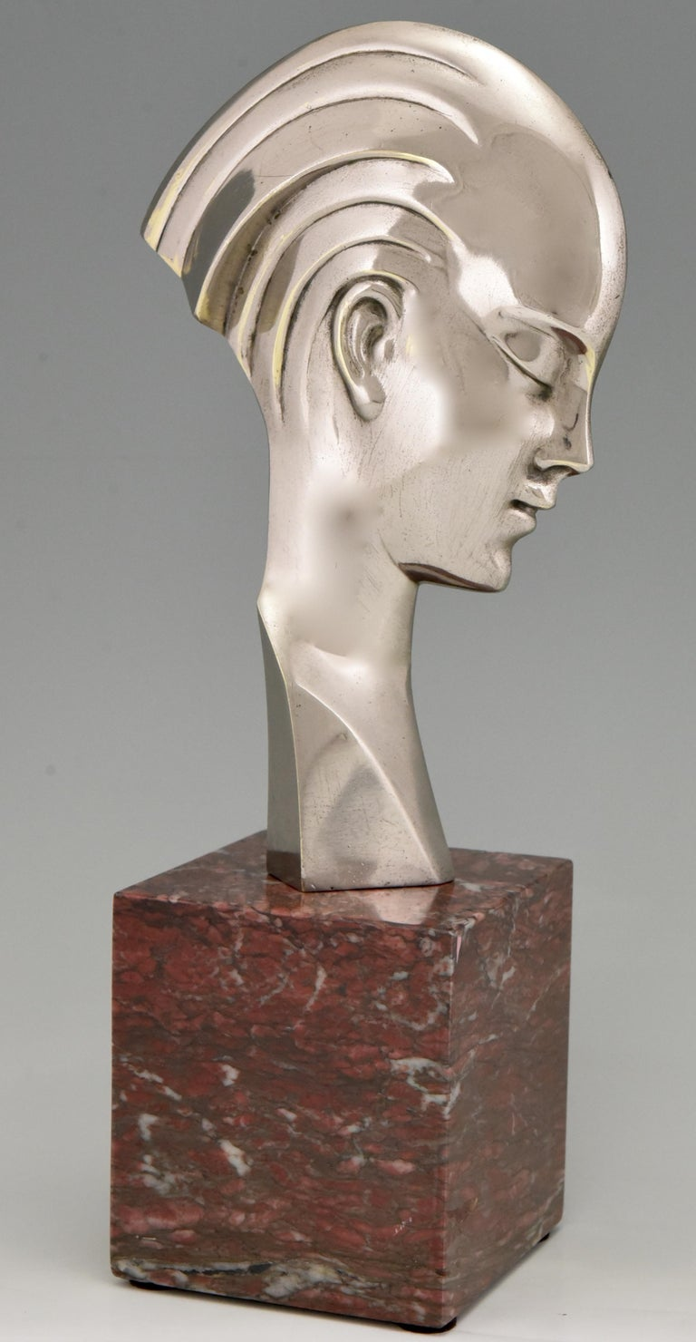 Stylish Art Deco bronze bust of a woman in profile.  Attributed to Guido Cacciapuoti. The bronze has a silver patina and stands on a red marble base.  Italy 1930-1940.