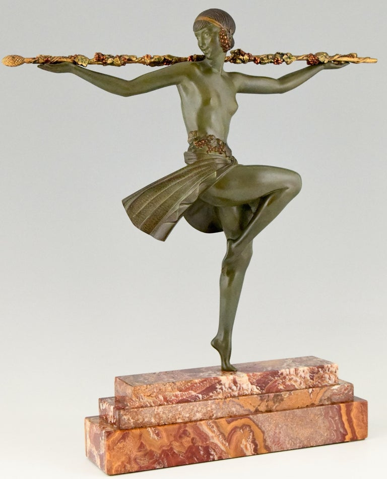 """Tall and elegant Art Deco bronze sculpture of a semi nude female dancer with Thyrsus. This bronze has a beautiful patina. The sculpture is mounted on a stepped marble base. France 1930.  This bronze is illustrated in the following books:? """"Art"""