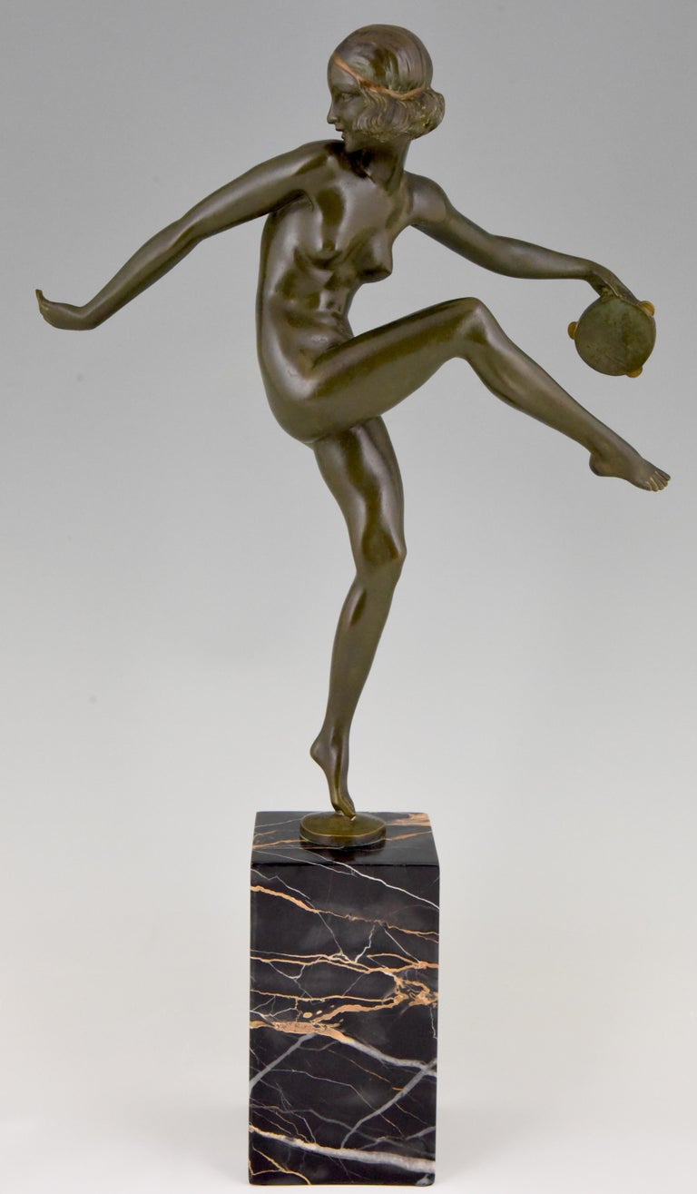 Elegant Art Deco bronze sculpture of a dancing nude with tambourine. The bronze has a lovely patina and stands on a Portor marble base. The sculpture is signed Laurel, pseudonym of Pierre Le Faguays, is numbered and has the foundry mark of Marcel