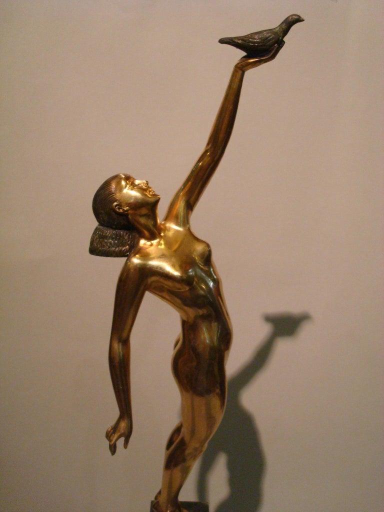 Gilt Art Deco Bronze Sculpture of a Nude Figure Holding a Dove by Pierre Le Faguays For Sale
