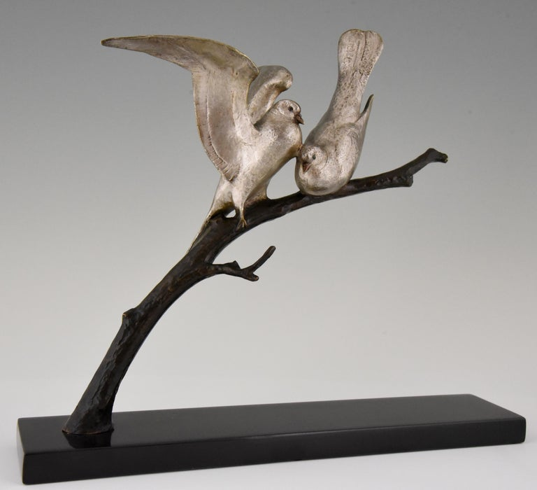 Lovely bronze Art Deco sculpture of two lovebirds sitting on a branch by the French sculptor Andre Vincent Becquerel. The bronze has a silver and brown patina and is mounted on a Belgian Black marble base. France circa 1930.   This model is