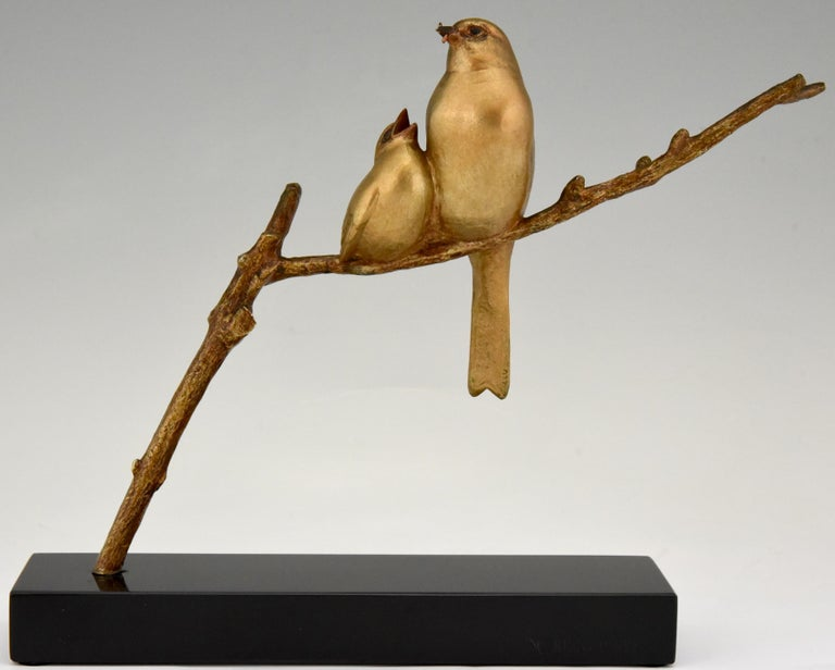 Art Deco bronze sculpture of a mother bird feeding her chick. Both birds are sitting on a branch. The bronze has a golden patina and stands on a Belgian Black marble plinth. Signed by the famous artist Andre Vincent Becquerel, France,