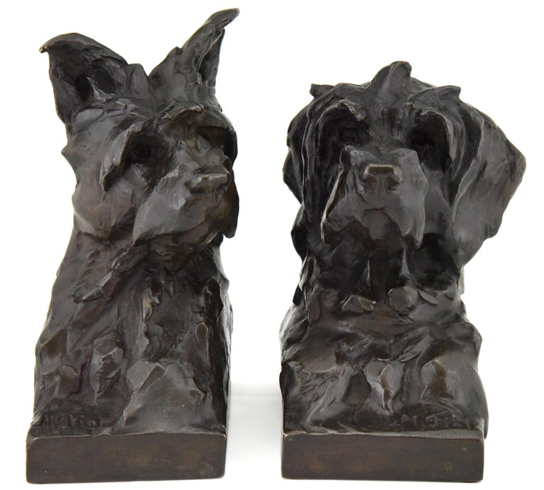 Pair of bronze bookends in the shape of terrier dog heads by the French artist Maximilien Louis Fiot, 1886-1953.  The sculptures have a beautiful patina and are signed by the artist as well as by the founder, Susse Freres. The dog busts are cast in