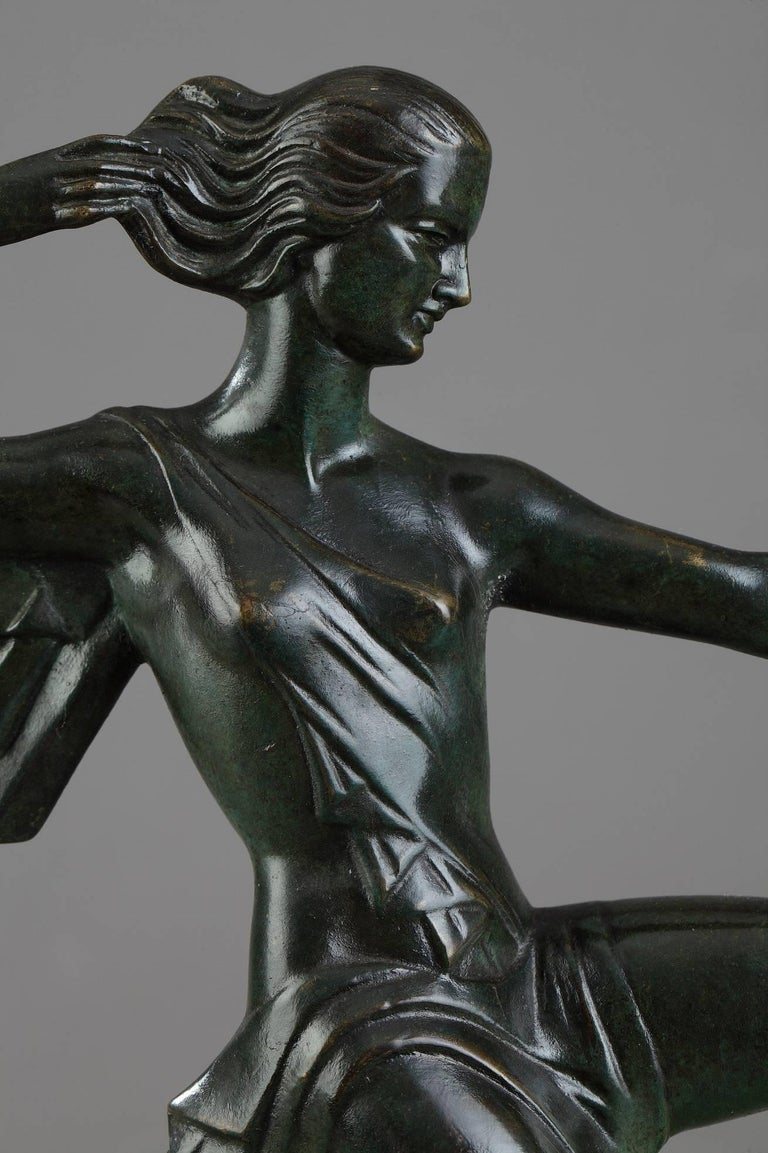 20th century bronze sculpture with green patina. It depicts a young woman pulling back the string and aiming an arrow with a longbow. She is set on a wide rectangular onyx and Portor marble base. Signed on the drapery, in the back : Gual and on the