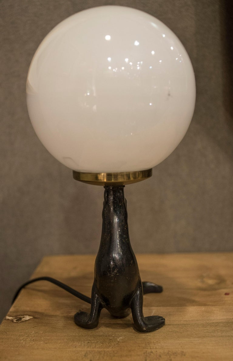 Awesome French Art Deco table lamp with a amazing bronze seal figure and a glass globe. In a perfect condition.