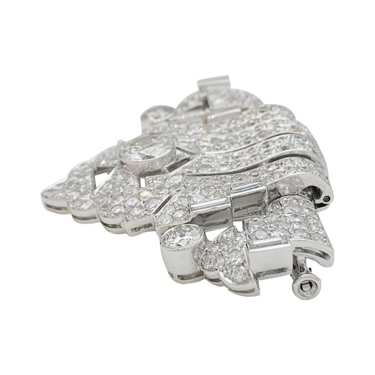 A 950/000 platinum and 750/000 white gold Art Deco brooch set with old cut and rose cut diamonds. The brooch and the clip can be dissociable. Width: 49mm Height: 36mm Weight: 19,2 grams