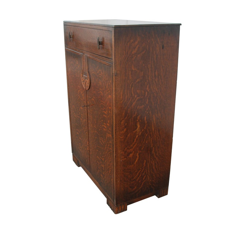 Art Deco Tiger Oak Cabinet  Features a light gold finish on interior shelves, as well as a locking mechanism with key for the large cabinets. Top drawers do not lock.   Carved wood on handles and legs.