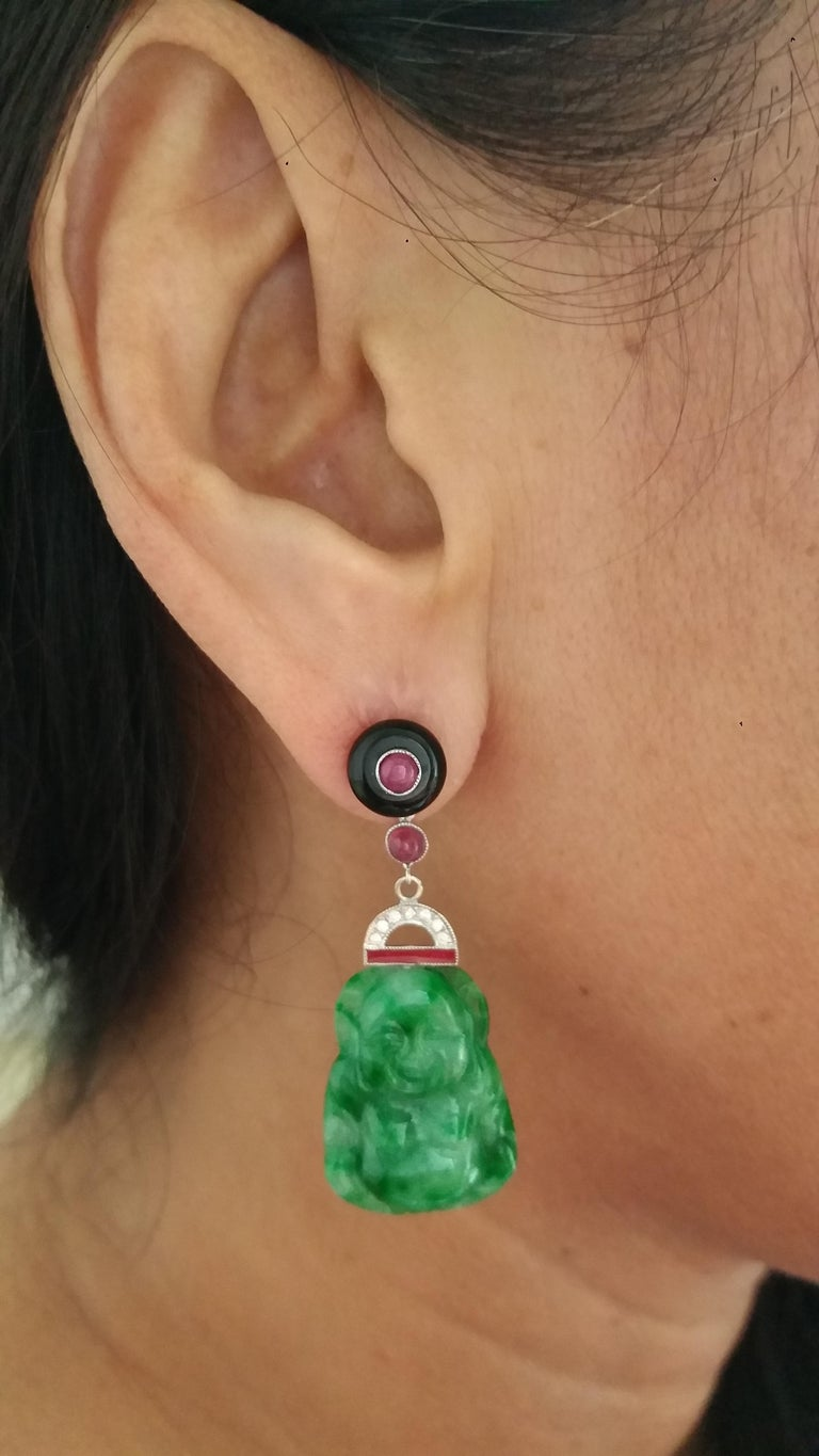 2 round Black Onix buttons tops with small round rubies cabochons in the center,central parts in white gold,small round rubies,14 round full cut diamonds,red enamel,and 2 Burma Jade Buddhas Length 47 mm Width 16 mm Weight 9 grams In 1978 our