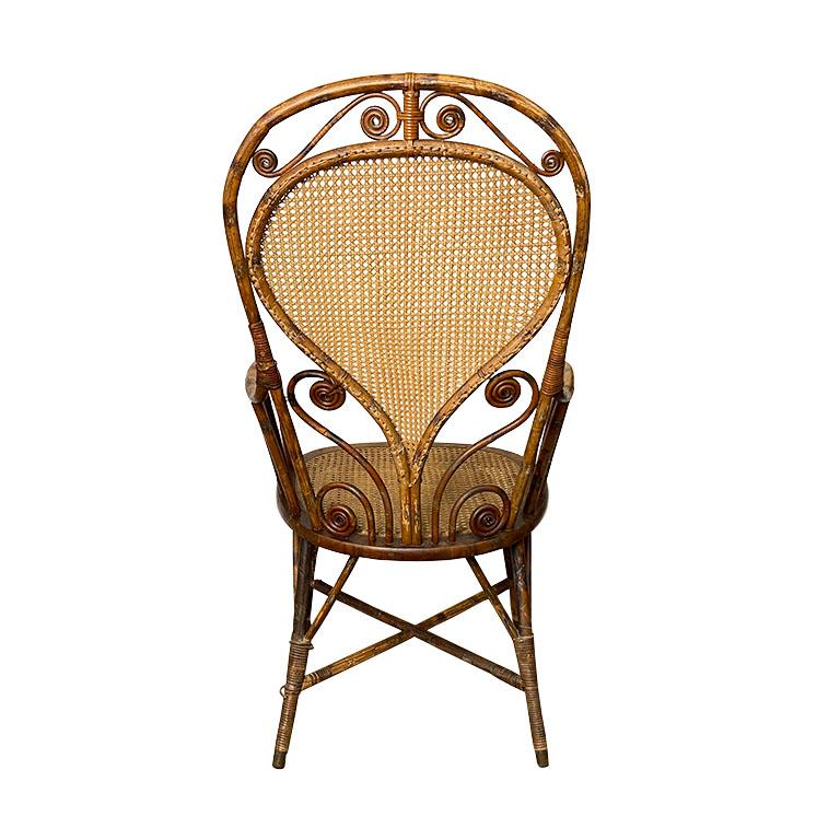 A gorgeous art deco burnt bamboo armchair. A stunning example of craftsmanship during the era, this piece is created from a mixture of cane, rattan, and burnt bamboo or