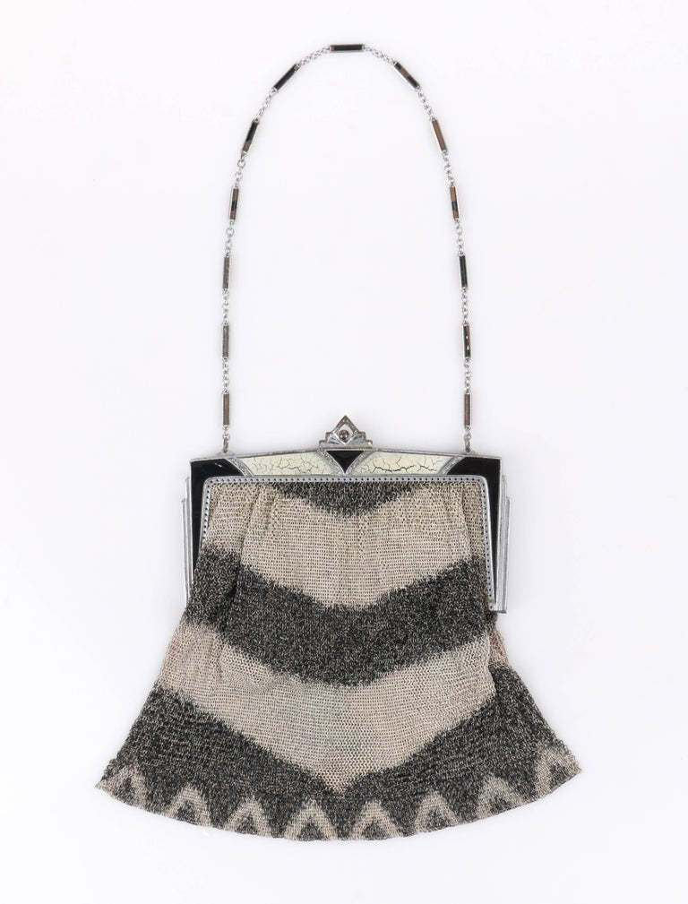 Vintage Art Deco c.1920's gray metal mesh enamel frame top flapper evening purse. Taupe and charcoal gray chevron patterned metal mesh body. Silver-toned metal frame top with black and beige enamel and carved filigree detail. Pointed art deco kiss