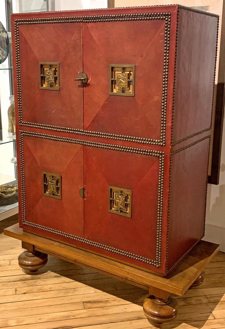 Beautifully proportioned, constructed and finished, this unique and remarkable Art Deco cabinet is covered with leather dyed a rich, deep red color, and features four Art Deco bronze mounts depicting nude figures celebrating Music and Art. The