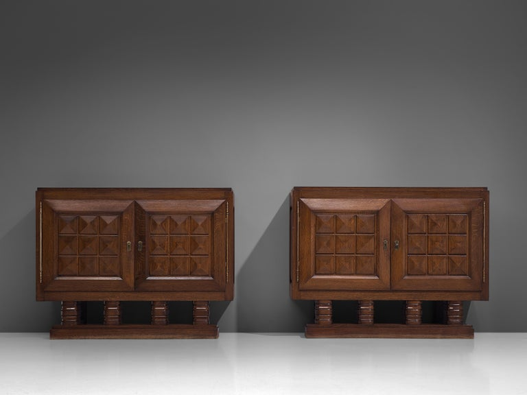 Art Deco cabinets, stained oak, brass, France, 1930s  Sturdy identical credenzas in oak with graphical door panels. These sideboards are equipped with several shelves which provide plenty of storage space. The door panels and base show the great