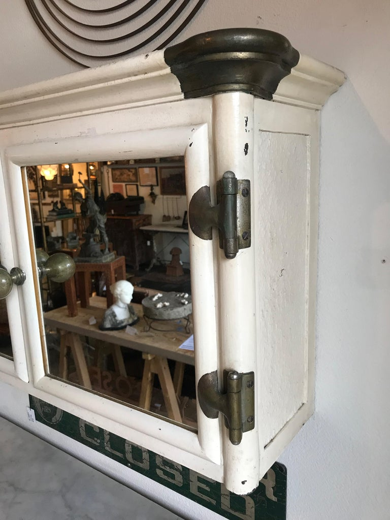 This is an Art Deco painted cast iron wall mount mirrored medicine cabinet from England. Oversized brass knobs, corner caps, and hinges make this incredibly attractive and unique. The interior is missing its shelves, however glass shelves can easily