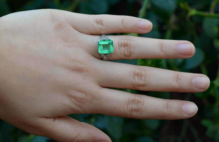 The Palm Springs Art Deco Engagement Ring. Glowing with an inner fire, this spectacular, Certified 5.47 Ct Colombian Emerald is sure to make all jewels green with envy. A classic Emerald cut set in a sleek, minimalist platinum setting enriched by