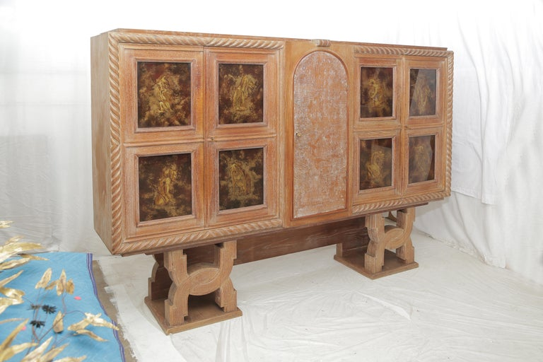Important cabinet in cerused golden oak .The left inside part of the piece would be more dedicated to be a dry bar. The main part of the piece (47 inches.) stands on a wooden carved base (Height: 20 inches).