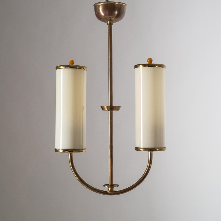 Charming small two anchor-shaped 1930s Art Deco chandelier. Two ivory-colored glass tubes with brass hardware and bakelite finials. Fine original condition with a nice patina on the brass. Two original bakelite E27 sockets with new wiring.