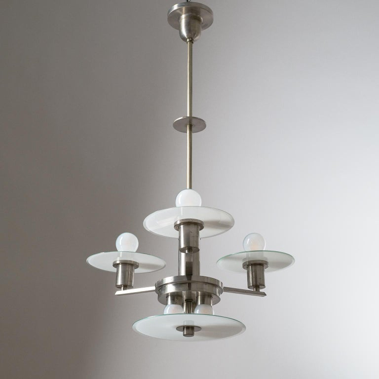 Rare geometric Art Deco or Bauhaus chandelier, circa 1930. Nickeled brass hardware with unusual glass shades, which are clear on one side and have a white casing on the other, along the rim the white casing has been 'shaved' off so that the rims are