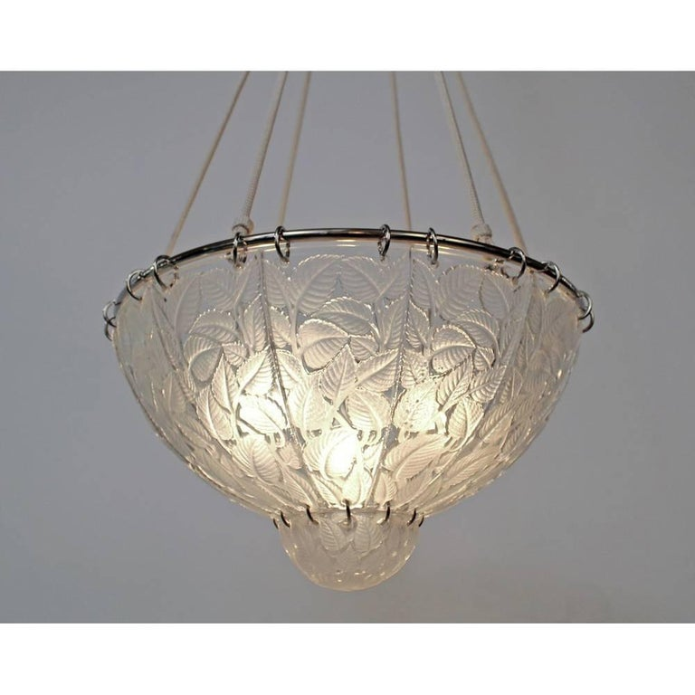 A clear and frosted molded glass chandelier by R. Lalique in the Feuilles de Charme design, depicting foliage Made in France  Model created in 1921 Signature: R. Lalique Reference: Lalique by Marcilhac, page 642.
