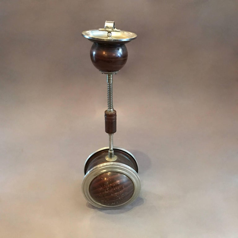 Art deco, chrome and faux wood finish metal, standing ashtray features a weighted ball base that allows the stem to tilt freely in a moving environment