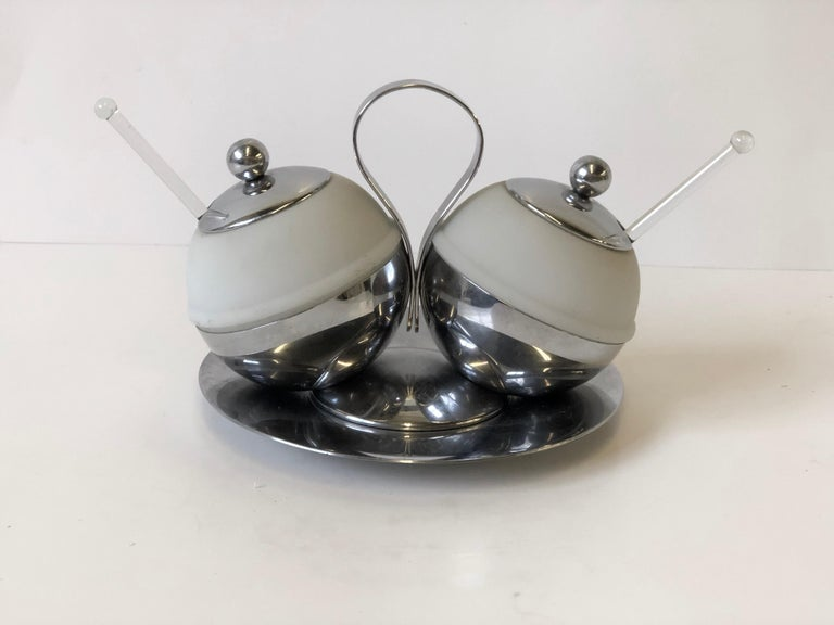 Rare 1930s Art Deco serving piece that could be used as a cream and sugar or salt and pepper set that is made of chrome and frosted glass. The set includes the lidded double server on stand, a plate rest, and a pair of glass spoons. The set was made