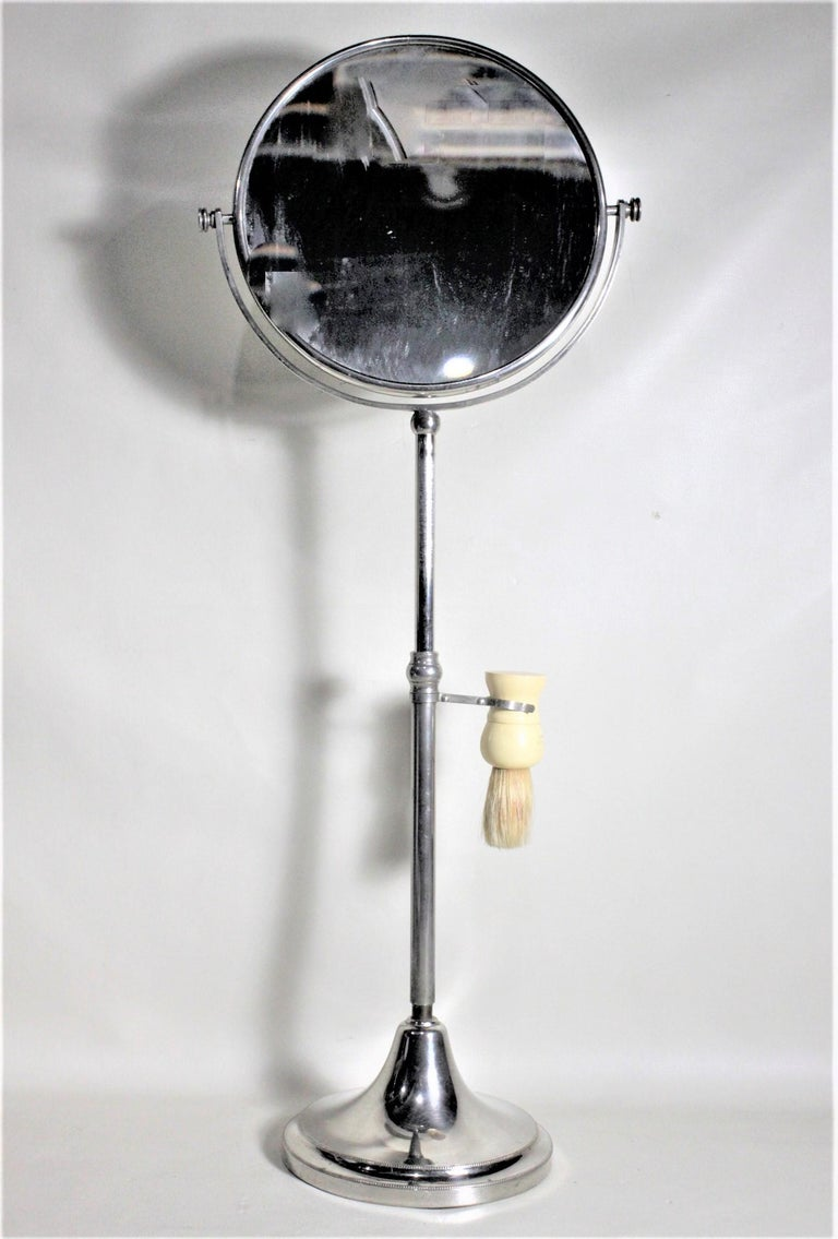 This chrome or nickel-plated pedestal shaving stand is unsigned, but presumed to have been made in the United States in the 1930s in the Art Deco style. The stand is well constructed and sturdy and has a screw down adjustment in the middle to allow