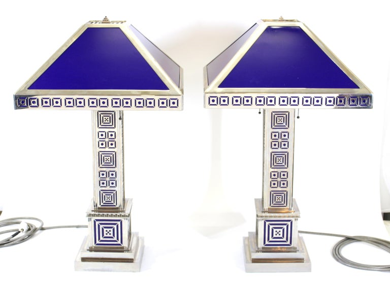 Art Deco pair of table lamps in chromed metal with modernist geometric latticework detailing and chromed metal shades with blue resin panels.