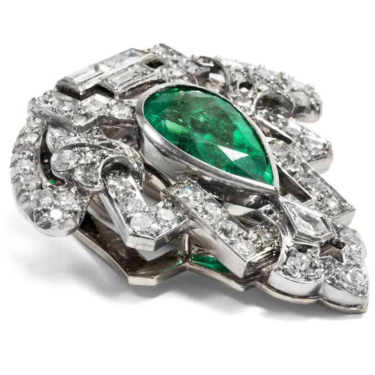 This clip brooch dates to the years around 1930 and embodies the modern spirit of the times par excellence. Gleaming diamonds and white platinum are united in an abstract triangular shape with a deep green emerald at its centre. The emerald is cut